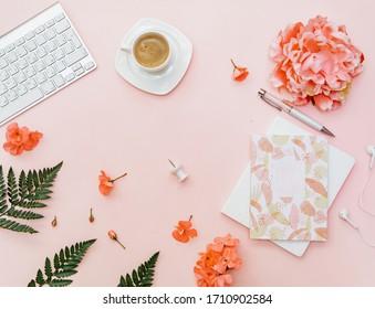 Top-Ansicht Freelancer Büro-Schreibtisch. Bloggerarbeitsplatz mit Kaffee, Tastatur, Blumen und Schreibtisch auf rosafarbenem Hintergrund