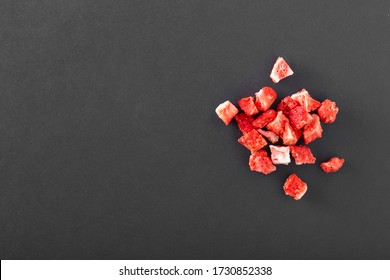 Top view of freeze dried fruit crispy cracked strawberry pieces isolated on black background with copy space text area. Dark photography concept.