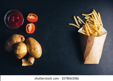 Top view of French fries with ketchup and raw potatoes on black bacground. copy space