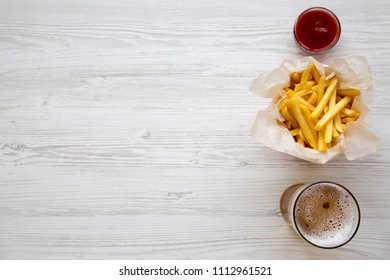 Top view french fries with ketchup and cold beer over white wooden background. From above. Copy space.