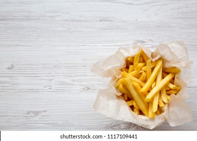 Top view, french fries over white wooden surface. Copy space and text area.