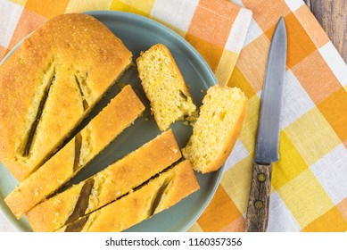 Top view of fresh baked cut hatch chili pepper cornbread on a plate.