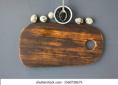 Top view of fresh black caviar with quail eggs over the wooden background