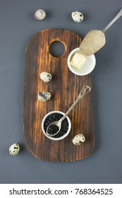 Top view of fresh black caviar with quail eggs over the wooden background.