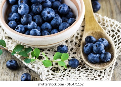Top view of fresh blueberries in a clay dish with wooden spoon on old wooden background