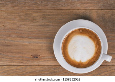 top view of fresh cappuccino on wood oak table