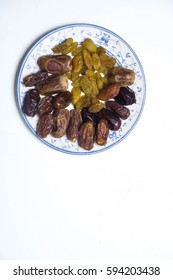 Top view of fresh dates and raisins on white plate isolated on white background. Selective focus.