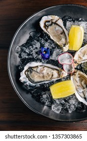 Top view of fresh Fine de Claire Oyster and lemon served in black bowl with ice on wooden table.