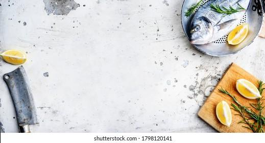 Vue de dessus de poisson frais dans une poêle au citron et au romarin sur une table rustique de cuisine blanche. Préparation du dîner en mer d'en haut. Bannière de design de menu de restaurant de luxe avec fruits de mer sur fond texturé.