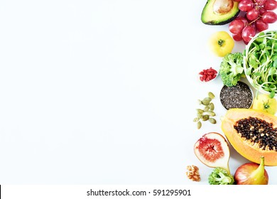 Top view of fresh fruits, vegetables, seeds, nuts and superfoods on white board with empty space. Vegetarian or clean-eating concept.