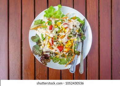 Top view of fresh garden salad with tomatoes, carrots, corn and dressing on a table. A mixture of small pieces of vegetable in a dish.
