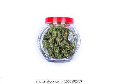 Top view of fresh green buds or flowers of cannabis (marijuana) weed in a transparent glass jar isolated on white background. Alternative treatment. Medical cannabis.