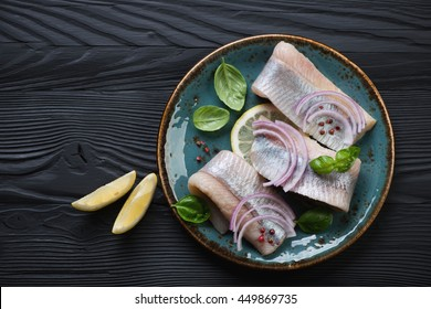 Top view of fresh herring fillet on a black wooden background