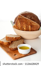 Top view of fresh homemade french bread loaves in banneton proofing basket and cup of olive oil on wooden cutting board. Bakery flat lay on white background