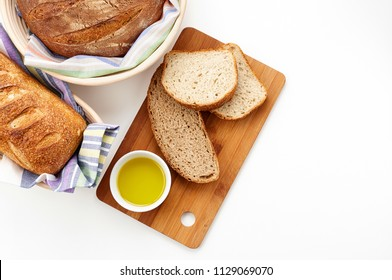 Top view of fresh homemade french bread loaves in banneton proofing basket and cup of olive oil on wooden cutting board. Bakery flat lay on white background with copy space