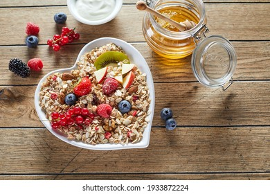 Top view of fresh honey and yogurt placed on wooden table near heart shaped bowl of muesli with pieces of fruits and berries in morning