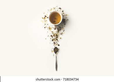 top view of fresh organic herbal tea in cup and spoon with dry herbs on white