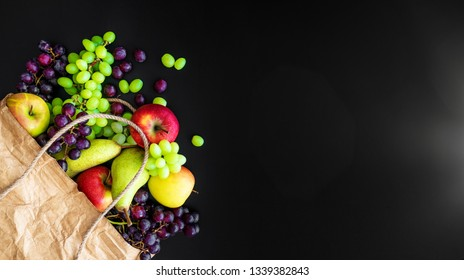 top view of fresh organic local fruits in brown paper bag on dark background