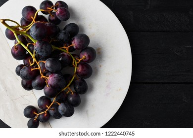 Top view of fresh ripe black grapes on white marble serving plate on black wooden table with copy space. Close up.