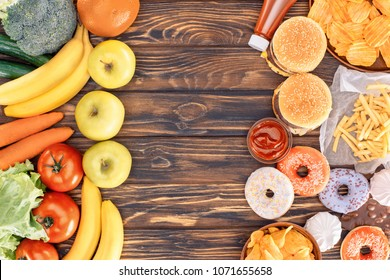 top view of fresh ripe fruits with vegetables and assorted junk food on wooden table