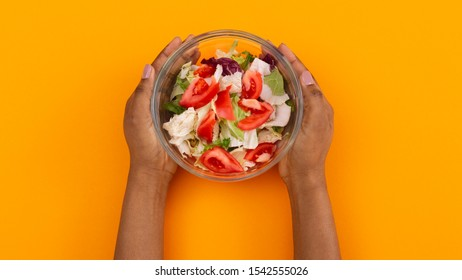 Top view of fresh salad bowl in black female hands over orange background, panorama