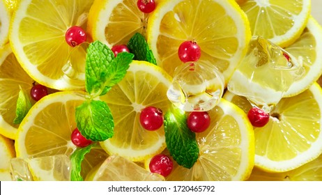 Top view of fresh sliced lemon, mint, berry and ice rotation. Close up.