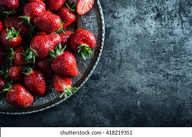 Top of view fresh strawberry in wrought plate on concrete board.