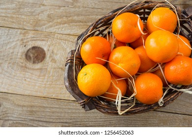 Top view. Fresh tangerines on a wooden background. Mandarins in a basket with copy space for text. Ripe and tasty tangerines. Clementines on a wooden table. Background tangerines.