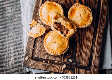 Top view of Fresh Traditional Australian meat mini pie on the wooden board on table background, closeup with copy space,rustic style. Delicious food