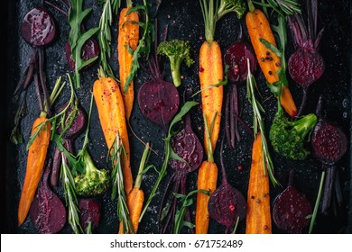 Top view of fresh vegetables, spices and herbs for roasting on rustic dark background, top view