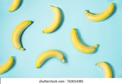 Top view of fresh yellow bananas isolated on blue background.