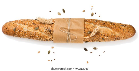 Top view of freshly baguette baked bread in paper with different seeds ( pumpkin, poppy, flax, sunflower, sesame, millet ) and wheat ears isolated on white background.