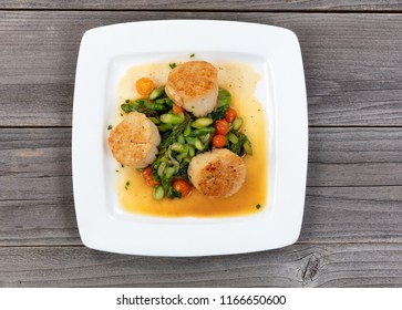 Top view of freshly cooked scallops and vegetables on rustic wooden table