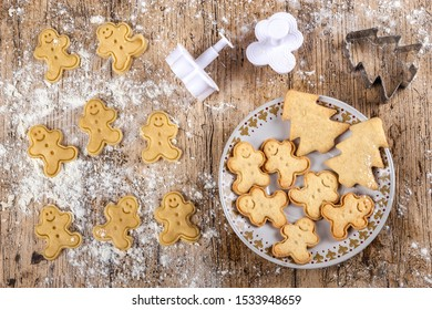 Top view of freshly cut cookies shaped like funny gingerbread dolls on a floured wooden table. Some baked cookies are placed on a plate. View from above. Recipes for children. Christmas desserts