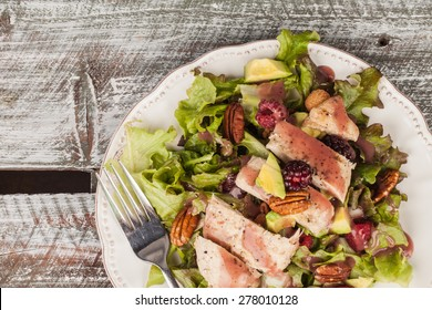 Top view of freshly harvested lettuce, grilled chicken, avocado, raspberry, pecan salad on an old weathered barn wood table background