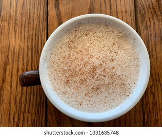 Top view of a freshly made, frothy mug of chai latte at a gourmet coffee shop.