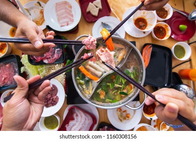 Top view of Freshly sliced pork meat with chopsticks over hot pot and vegetables for shabu and Japanese food.