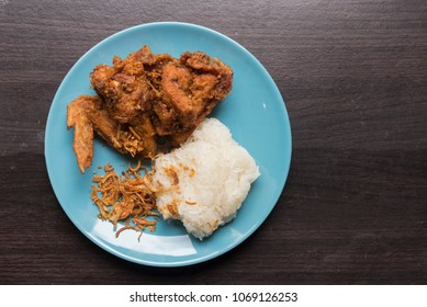 Top view Fried chicken and sticky rice in the light blue dish on brown wooden. fried chicken the most famous food of Hat-yai Songkhla Thailand.