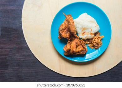 Top view Fried chicken with sticky rice in the light blue dish on light brown wooden. fried chicken the most famous food of Hat-yai Songkhla Thailand.that tourist want to eat.