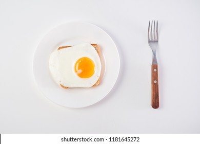 Top view of fried egg on white plate on white background with fork