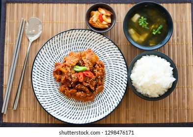 Top view of fried pork with spicy korean sauce (bulgogi) with rice and kimchi - korean traditional food.