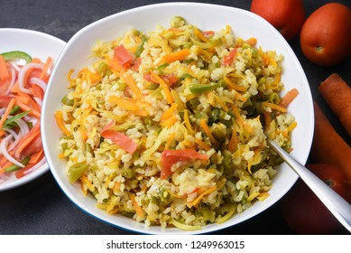 Top view of fried rice or veg pulao, vegetable biryani with ingredients  brown rice, vegetables carrot, beans, tomato, capsicum, onion in Mumbai, India. Cooking oil free food for healthy diet.
