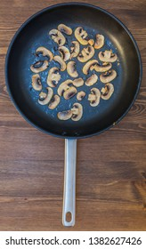 top view of fried sliced champignons on a black frying pan with pan handle on a wooden table top