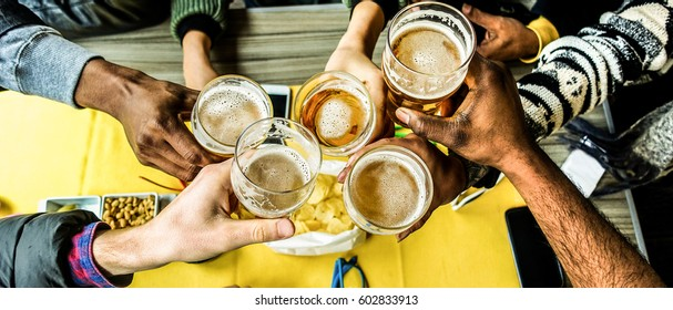 Top view of friends cheering with home brew in pub bar restaurant - Young people hands toasting and beers half pint - Party concept - Warm filter - Focus on bottom hands glasses