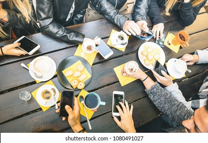 Top view of friends drinking cappuccino at coffee shop restaurant - People having fun together eating cakes and using mobile smart phones at cafe bar - Friendship concept on bright vintage filter