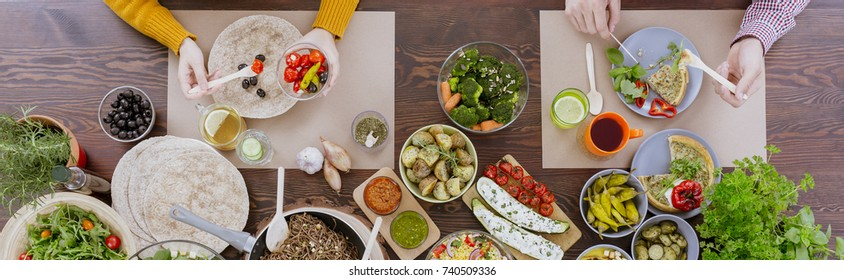 Top view of friends eating dinner during a meeting at a vegetarian restaurant