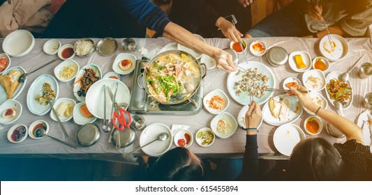 Top view of friends eating korean seafood hotpot and Kimchi