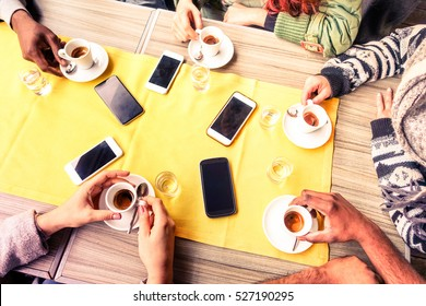 Top view friends hands drinking coffee espresso cup and mobile phones on table - Young multicultural people meeting at cafe bar indoor scene from above -  Winter concept of togetherness and technology