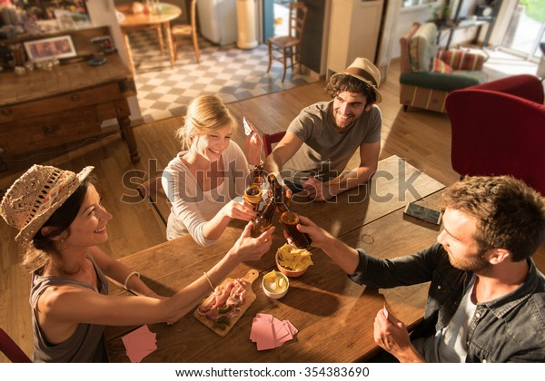 Top view of friends having a drink and playing cards on a sunny evening. They are sitting at a wooden table in a cozy house with beers and tortilla chips. They are wearing casual clothes and hats.