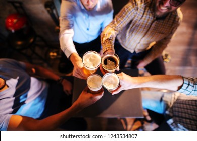 Top view of friends making a toast with beer. Pub interior.